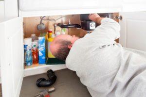 repairman fixing a garbage disposal